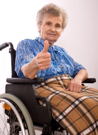 persona en silla de ruedas: retrato de una anciana en silla de ruedas de dar la se�al del pulgar arriba  Foto de archivo