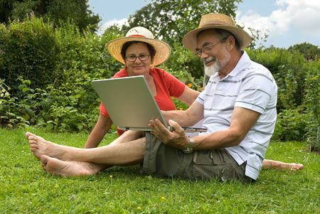 senior couple in garden at leisure with laptop computer photo