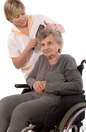 combing hair: Nurse dressing the hair of a senior woman