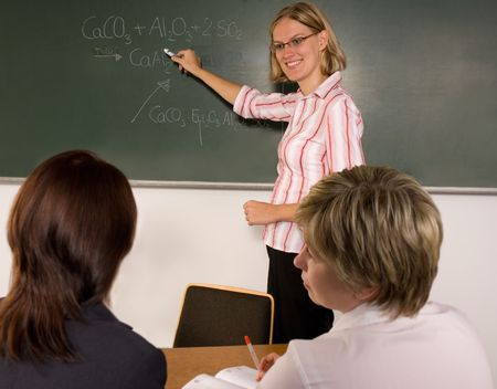 young student writing chemical formula at the blackboard Stock Photo