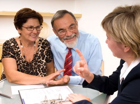 Mature couple talking to financial planner at home  photo