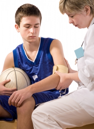 a teams doctor giving first aid the young sportsman Stock Photo