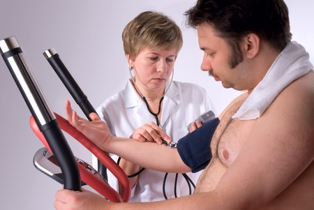 Senior is being observed by doctor after training, measuring blood pressure photo