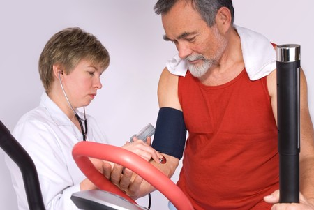 cardiovascular exercising: Senior is being observed by doctor after training, measuring blood pressure Stock Photo