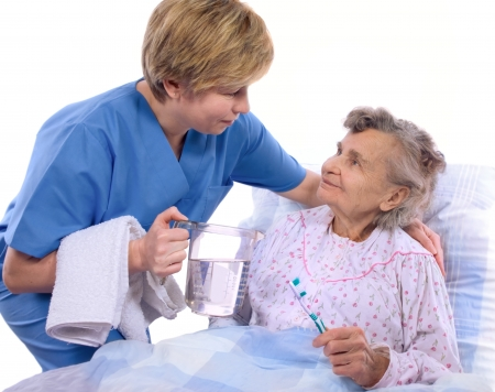 Nurse helps the senior woman in washing photo