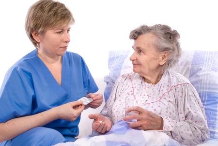 nurse gives the senior woman the midicine