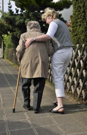 personas discapacitadas: Superior de la mujer caminando con la ayuda de una hija Foto de archivo