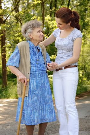 Senior woman walking with the help of a granddaughter  Stock Photo