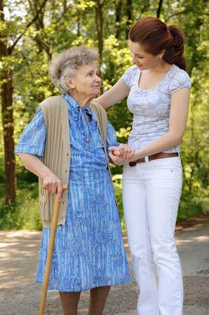 personas ayudando: Superior de la mujer caminando con la ayuda de una nieta