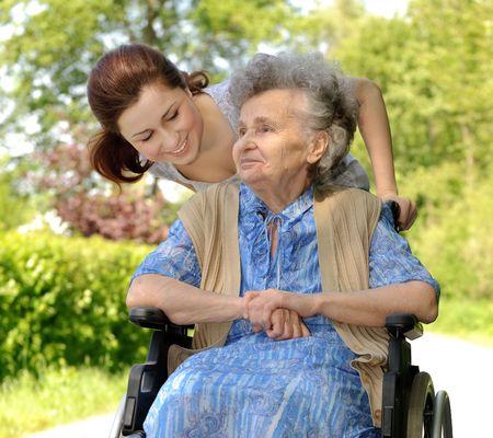 elderly pain: Senior donna in sedia a rotelle, con la sua nipote
