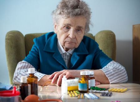 senior woman with her medicine bottles photo