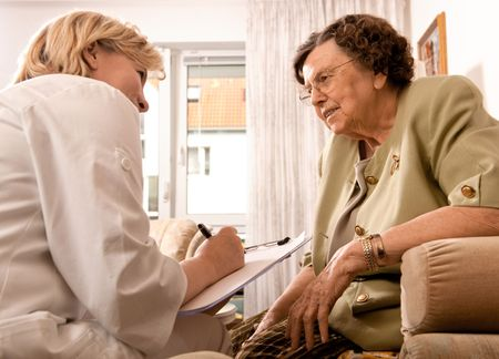 nursing bottle: Senior woman is visited  by her doctor or caregiver at home Stock Photo