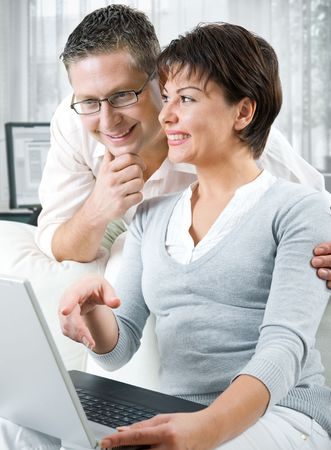 happy couple using laptop at home  photo