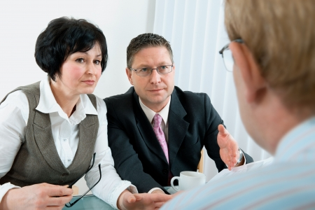 lawyer meeting: woman and her lawyer in conversation with husband during divorce process