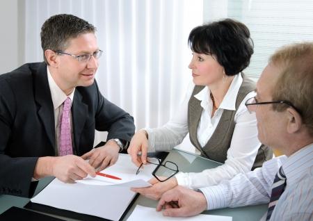 obligaciones: Reuni�n de altos de pareja con el agente o Asesor Foto de archivo