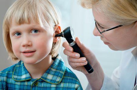 female doctor examining little child boy photo