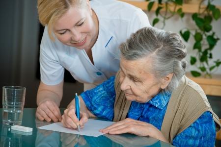 nursing treatment: Ayudar a una mujer senior por la enfermera en el hogar