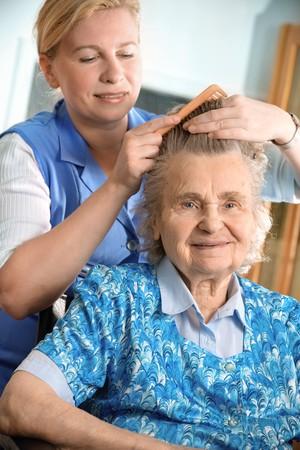 care home: Nurse dressing the hair of a senior woman