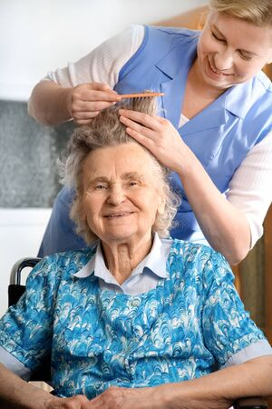 in home care: Infermiera apprettare i capelli di una donna senior  Archivio Fotografico