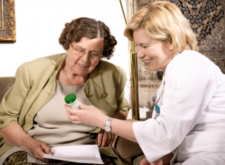 Senior woman is visited  by her doctor or caregiver at home Stock Photo - 7139021