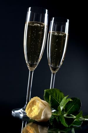 twee champagne flutes met een roos