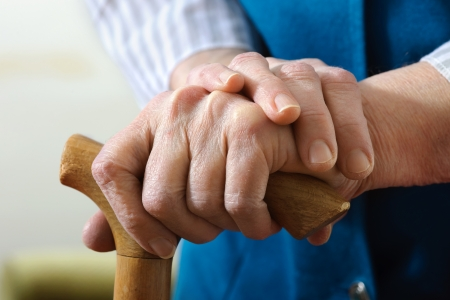 disabled person: hands of a senior woman on cane Stock Photo