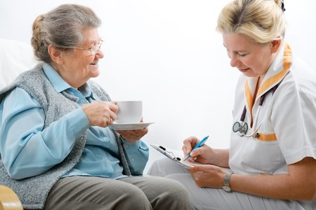 Senior woman is visited by her doctor or caregiver at home photo