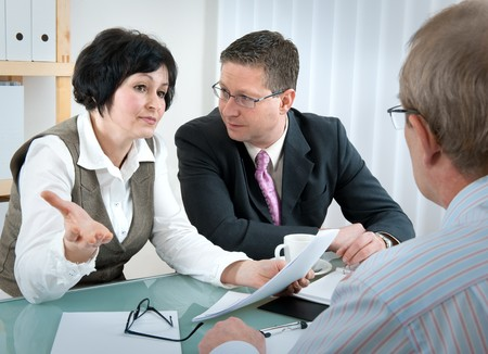 woman and her lawyer in conversation with husband during divorce process photo