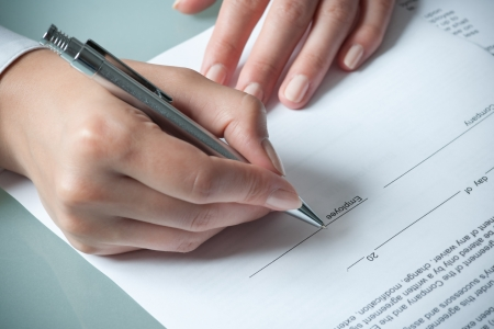 filling out: female hands filling out employment agreement contract Stock Photo