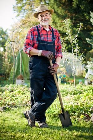Senior gardener with a spade in the garden Stock Photo