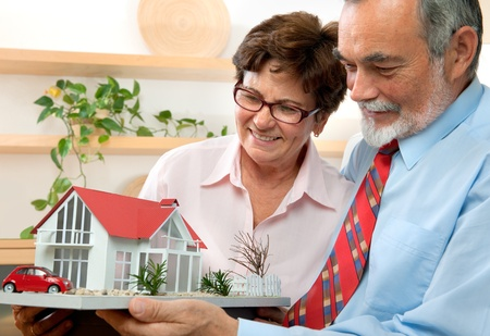 real estate planning: senior couple holding a model of their dream house Stock Photo