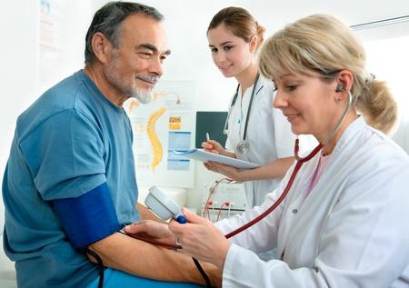enfermera con paciente: Paciente es siendo observado por el médico