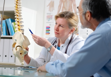 fisica: Doctor muestra las �reas con problemas en modelo de la columna vertebral a paciente  Foto de archivo