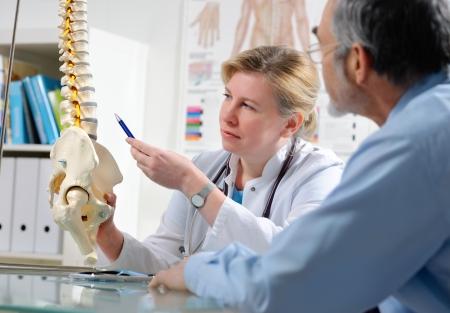 physical test: Medico mostra le aree di problema sul modello della colonna vertebrale al paziente