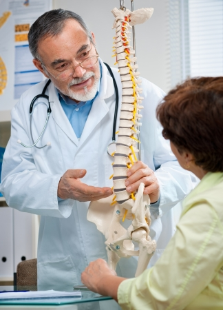 senior pain: Doctor shows the problem areas on the spines model to patient