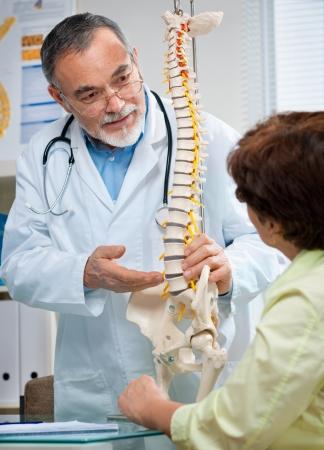 colonna vertebrale: Medico mostra le aree problematiche sul modello della colonna vertebrale al paziente
