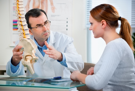 dolor de espalda: Doctor muestra las �reas de problema en modelo de la columna vertebral para el paciente