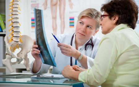 fisico: M�dico explicando los resultados de rayos x para el paciente Foto de archivo