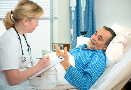 general practitioner: doctor or nurse talking to patient  lying in bed in hospital  Stock Photo