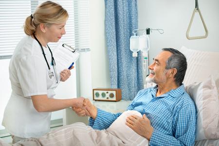 enfermera con paciente: m�dico hablando con un paciente senior en el hospital Foto de archivo