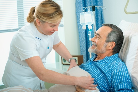 practitioner: Nurse cares for a patient lying in bed in hospital Stock Photo