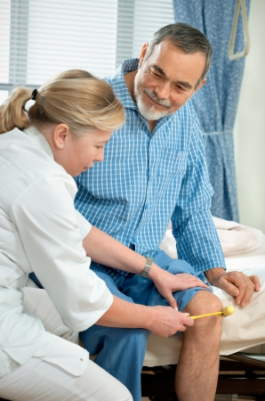 Physician checking reflexes of an old man in hospital Stock Photo