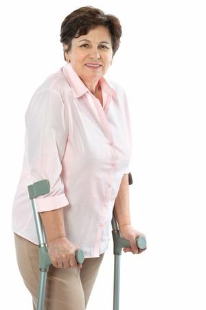 disability insurance: donna anziana sulle stampelle sorridente Archivio Fotografico