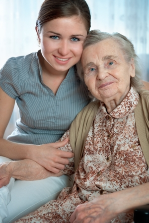 Senior woman with her home caregiver photo