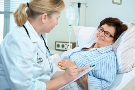 enfermera con paciente: médico o enfermera hablando al paciente en el hospital Foto de archivo