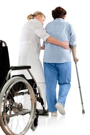 discapacidad: enfermera ayuda a una mujer senior en muletas