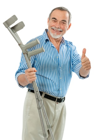 recovering: senior man holding the crutches smiling. Concept for recovering