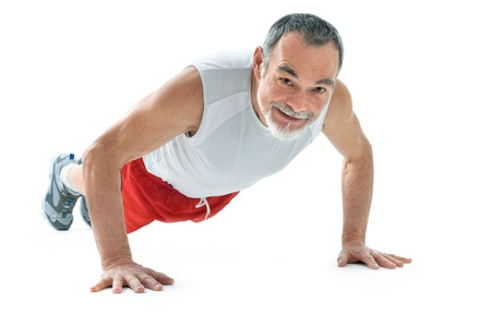 pushups: senior man doing push-ups exercise in gym. Stock Photo