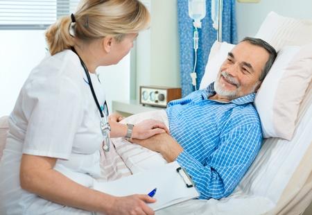 malade au lit: M�decin examinant un patient �g� � l'h�pital