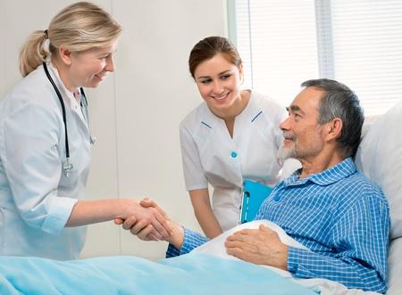 enfermera con paciente: Doctor sacude manos con el paciente en la cama de hospital
